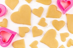 raw-homemade-heart-shaped-cookies-with-pink-cookie-cutter-flour_130458-627