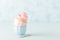 cupcake-with-gentle-pink-cream-decoration-two-cups-blue-pastel-background_76290-13