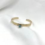 Jonc Meghan en plaqué or 3 microns martelé et serti dune pierre turquoise en forme de goutte. Bracelet rigide ajustable