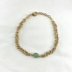 Bracelet composé d'une maille ronde parsemée de petites boules en plaqué or 3 microns et d'une pierre ronde semi-précieuse en aventurine.
