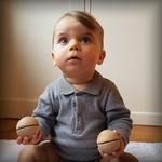 bébé assis avec 2 petites boules sonores