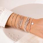 BR8642-3TCRIV.BR7441IV.BR8624CRIV.BR8266BSCR - poignet portant une composition de bracelets beiges et perles nacrées