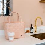CM panier tressé main rose pâle posé dans cuisine avec coffee to go handed by