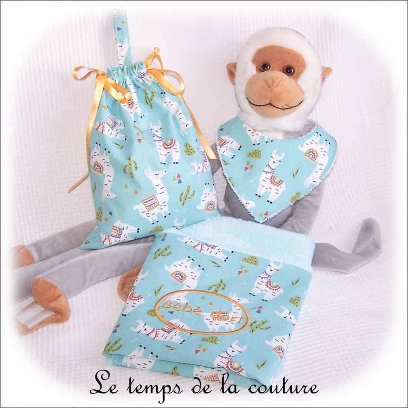 Ensemble naissance : couverture, pochon et bavoir bandana motifs lama, tons bleu vert d\'eau