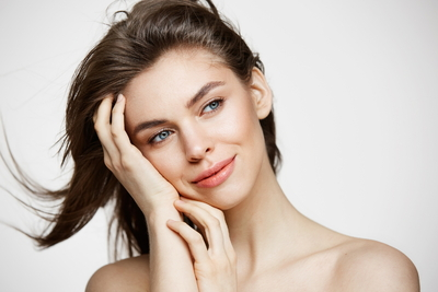 beautiful-naked-young-woman-with-perfect-clean-skin-smiling-touching-hair-over-white-wall-facial-treatment