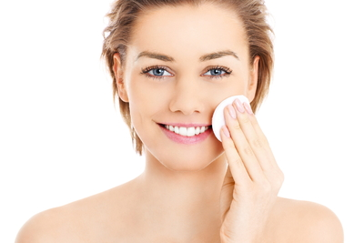 happy-woman-cleaning-her-face-with-cotton-pads-over-white-background