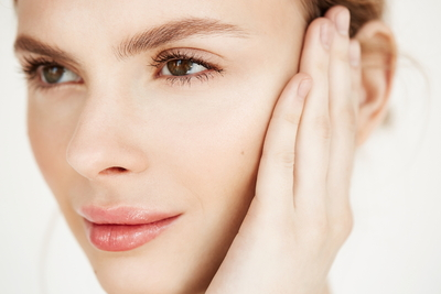 close-up-of-young-beautiful-girl-smiling-touching-face-spa-beauty-health-and-cosmetology-concept