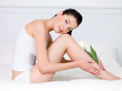 beautiful-young-woman-with-white-tulip-on-her-attractive-perfect-legs-indoors
