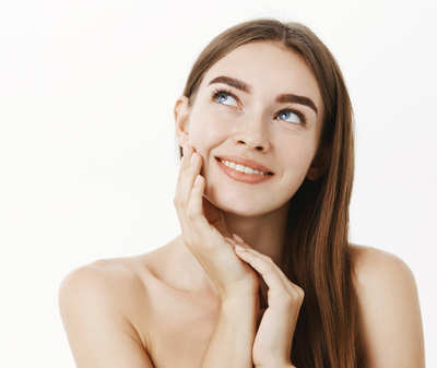 woman-applying-cream-on-face-feeling-skin-soft-and-tender-standing-dreamy-and-delighted-with-result-gazing-at-upper-left-corner-with-sensual-smile-touching-cheek-posing-naked-over-grey-wall