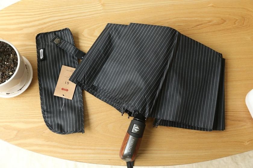 Parapluie pliant de qualité noir rayures sur table